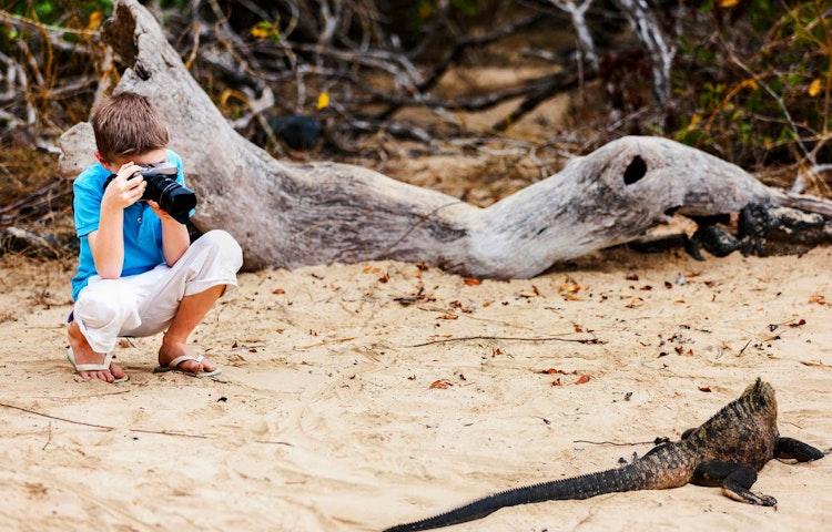 boy photographing iguana