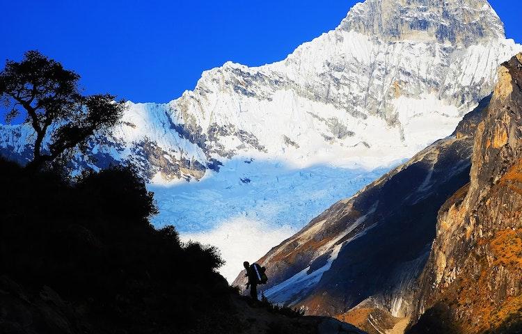 hiker silhouetted against snowy peak